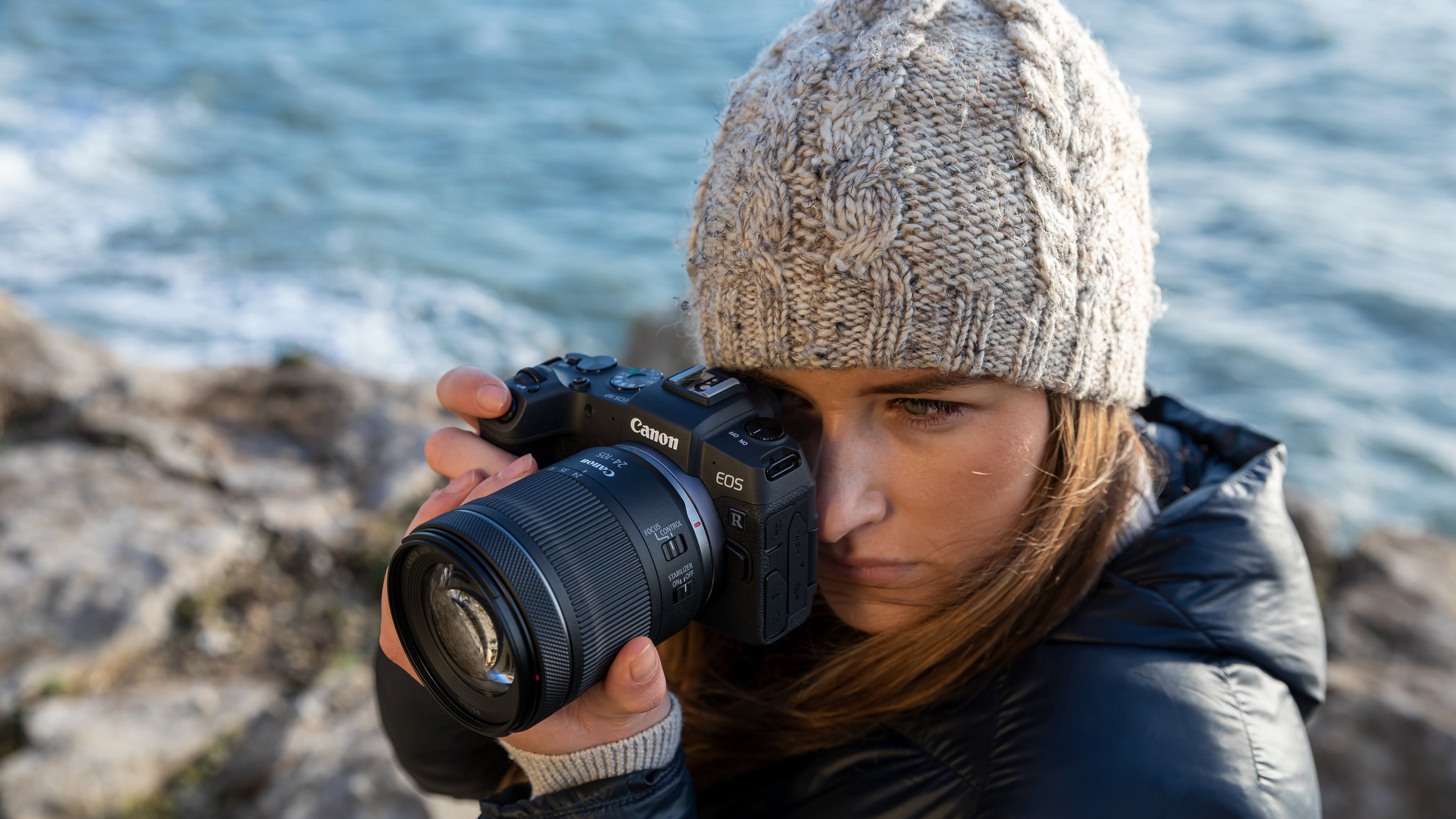 Canon RF 24-105mm F4-7.1 IS STM with on EOS RP being held by a lady wearing a grey beanie and blue jacket
